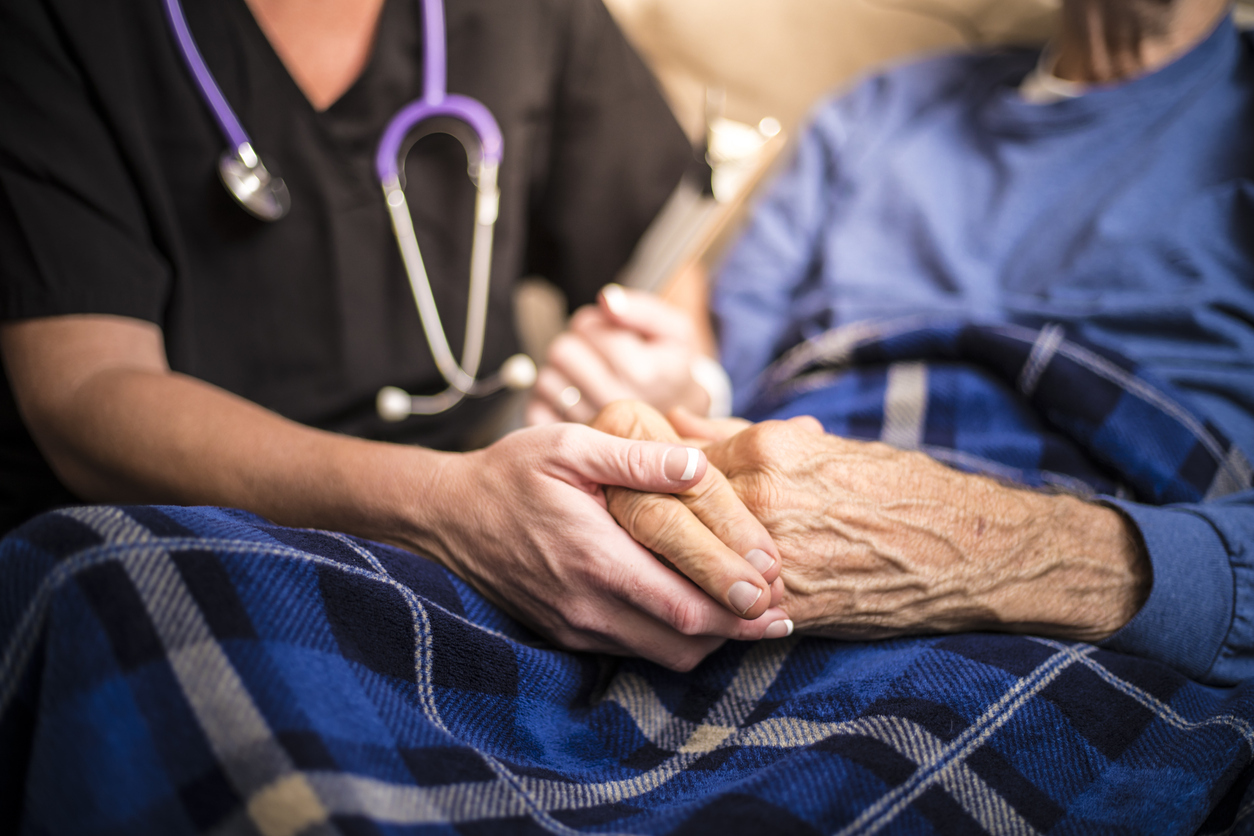 A nurse holding an elderly patient's hand