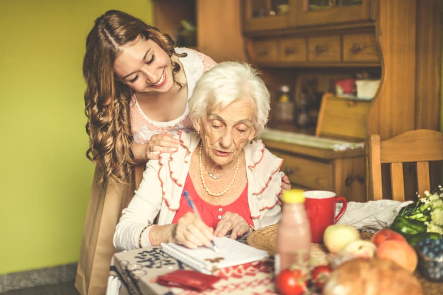 senior woman at kitchen table writing in notepad as a young lady smiling looks over her shoulder