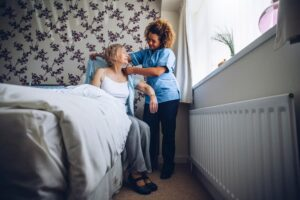 Newly Appointed Home Health Aide Assisting Woman Out of Bed