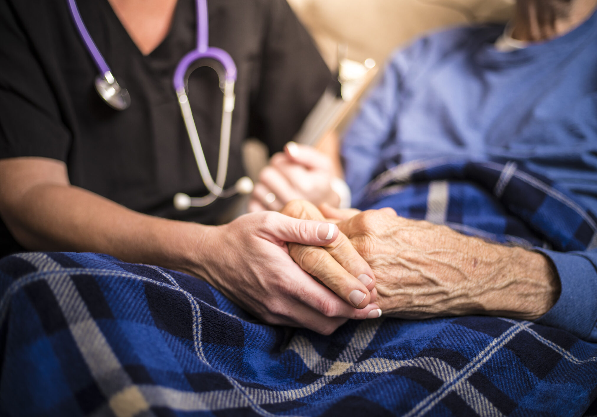 healthcare worker holding older man's hands